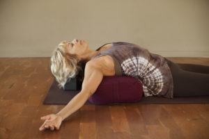 woman lying on yoga bolster